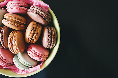 Macarons in a bowl on a dark background