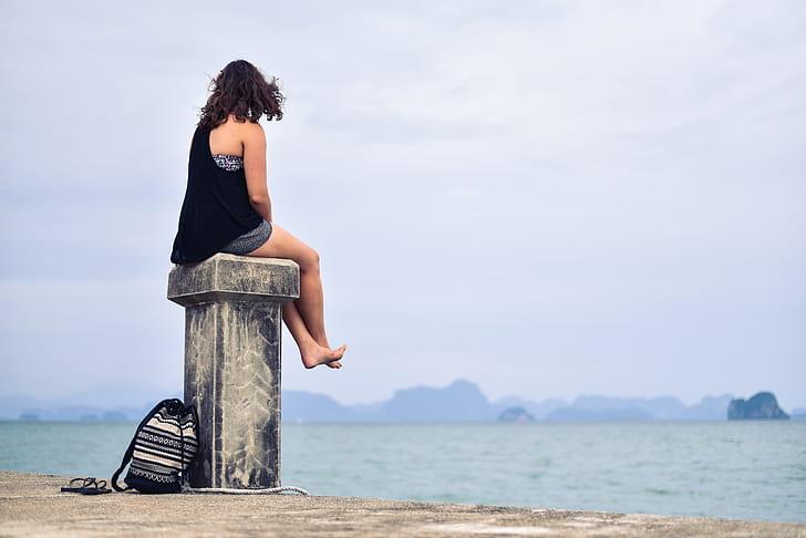 Royalty-Free photo: Woman in Black Shirt Sitting Near Body of Water during  Daytime | PickPik
