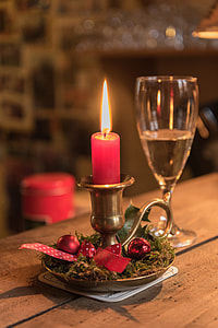 lighted red candle near champagne glass
