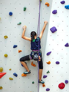 woman doing indoor wall climbing