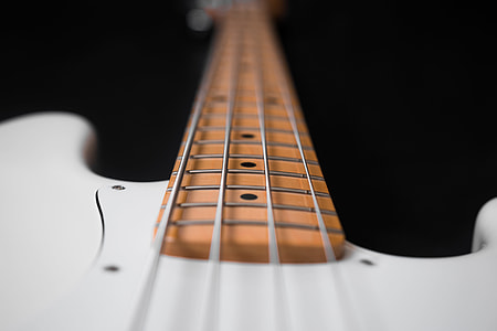 close-up photography of white 4-string bass guitar