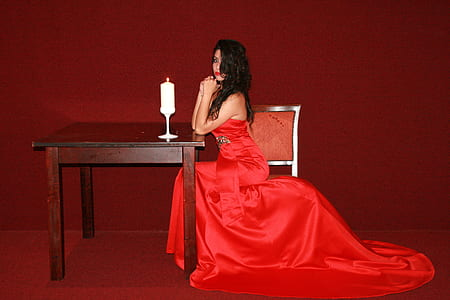 woman wearing red dress leaning on brown wooden table