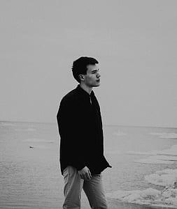 grayscale photography of man wearing dress shirt beside body of water