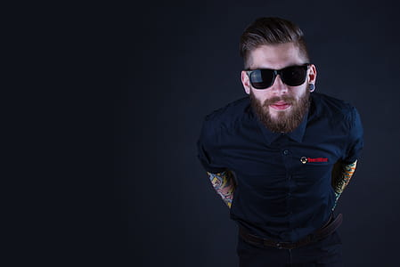 man wearing black framed sunglasses and black button-up shirt