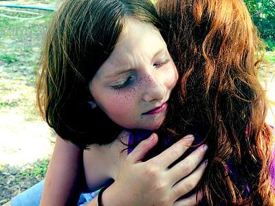 two girl hugging during daytime