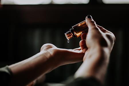 person pour a vial bottle on palm