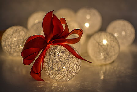 macro photography of yarn lamp with red ribbon