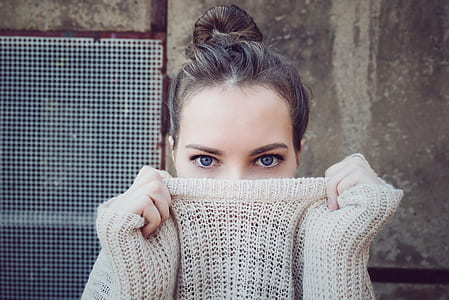 shallow focus photography of woman wearing gray sweater