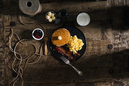 pancake with butter, scramble egg, and bacon served on black ceramic plate
