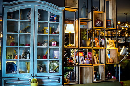 assorted decors in teal wooden display cabinet
