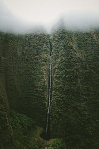 waterfalls near green trees under white clouds