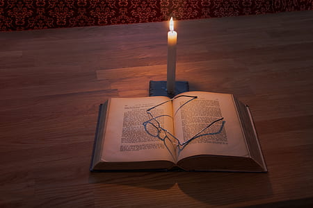 white taper candle and book on brown wooden table