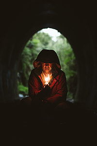 man wearing brown hooded jacket lighting a match in tunnel