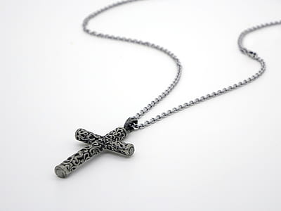 silver-colored and black cross pendant in silver-colored link necklace