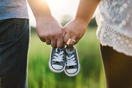 two person holding baby shoes