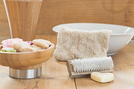 white towel on white ceramic basin with brown wooden brush
