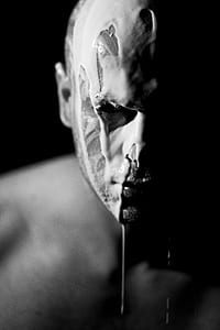 grayscale photo of man with white liquid on his face