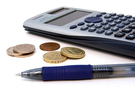 pen near coins and calculator