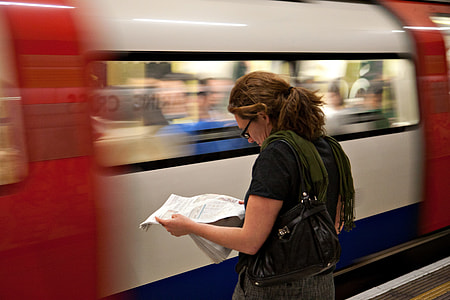 A woman reads the newspaper as she waits for her connection on the London Underground