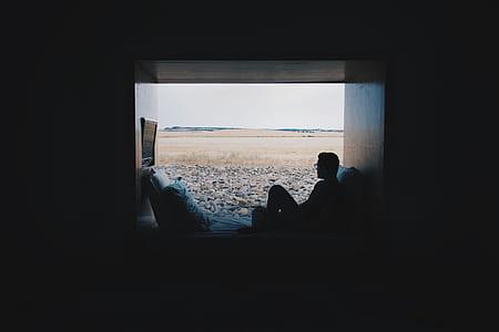man sitting on window