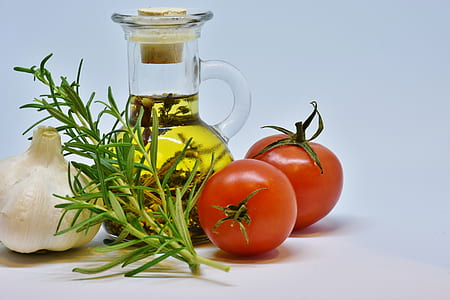 two red tomatoes, olive oil jar and white onion