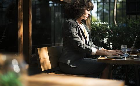 woman sitting on bench using laptop