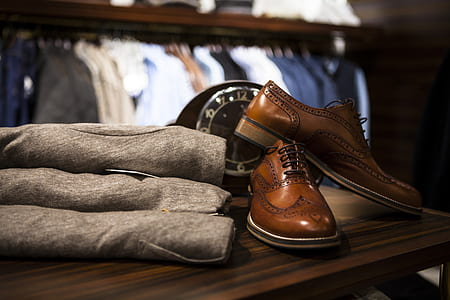 pair of brown leather dress shoes on brown wooden table