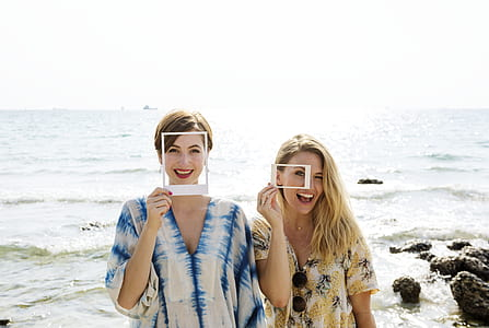 two woman holding white frames