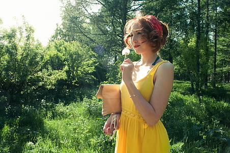 woman in yellow sleeveless dress near forest during daytime