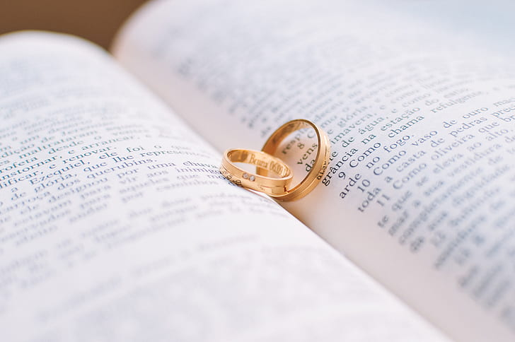 two gold-colored rings on book