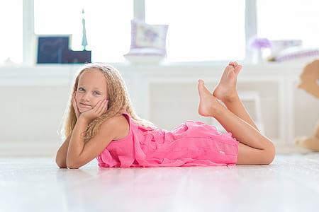 girl in pink dress lying on floor