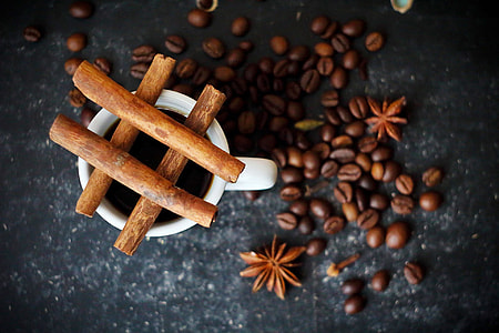 shallow focus of brown coffee beans beside white ceramic mug