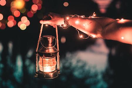 person holding black kerosene lantern