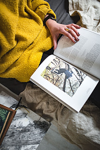 Young woman reading a magazine in bed