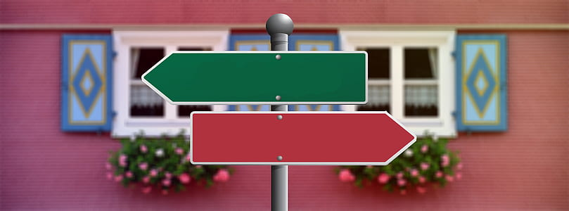 macro photography of green and red arrow signage