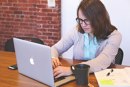 woman using silver MacBook Air on the table