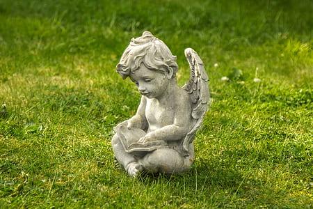 concrete cherub statue during daytime