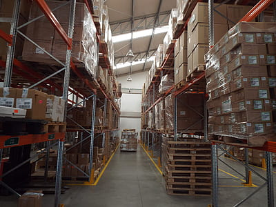 cardboard boxes piled on shelves inside warehouse