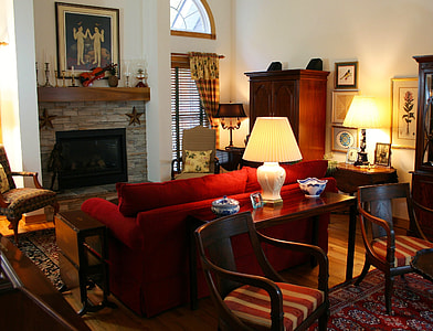 red fabric sofa in front of electric fireplace beside cabinet