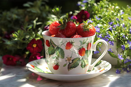 red strawberries on white ceramic teacup