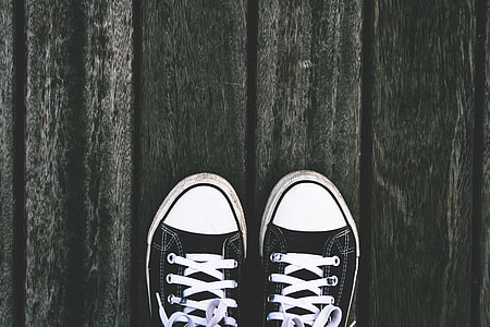 Persons feet and sneaker shoes on wooden panels