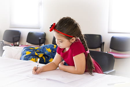 girl wearing red t-shirt writing on white printer paper on desk