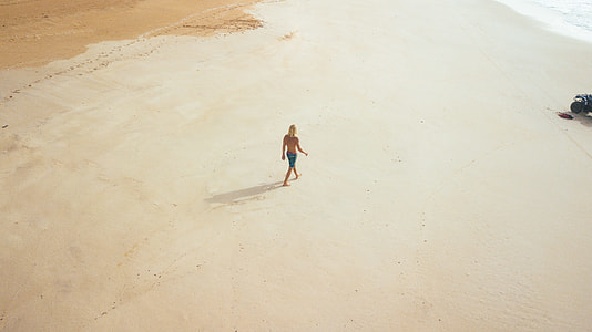 person walking on sand in aerial photography