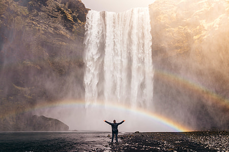 man in black long sleeve shirt in front of waterfalls