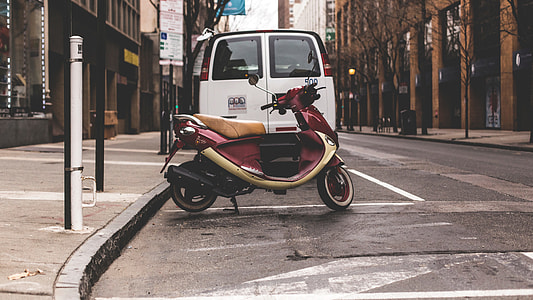 photography of red motor scooter near white van and brown concrete buildings