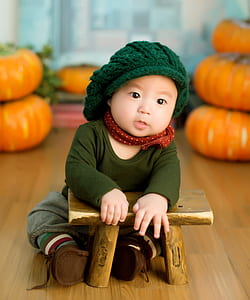 baby wearing green knitted cap, green crew-neck long-sleeved shirt and brown pants sitting near brown stool