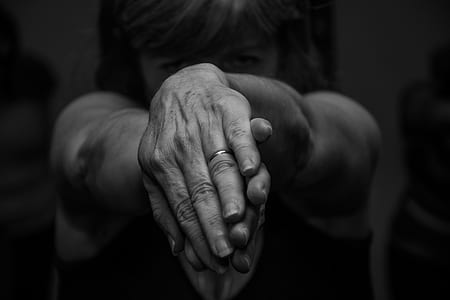 grayscale photography of woman twisting both hands