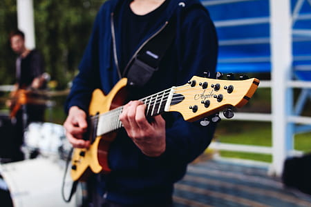person holding brown guitar