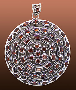 silver-colored and red gemstone pendant