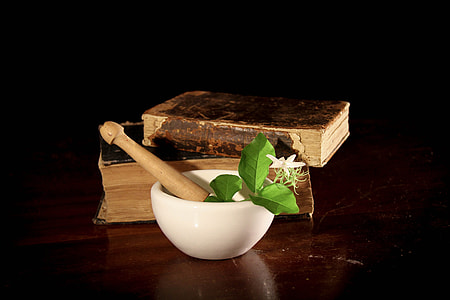 white and brown mortar and pestle beside two brown hardbound books